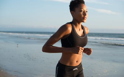woman running on the beach in a sports bra