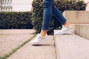Legs of woman wearing sneakers walking downstairs