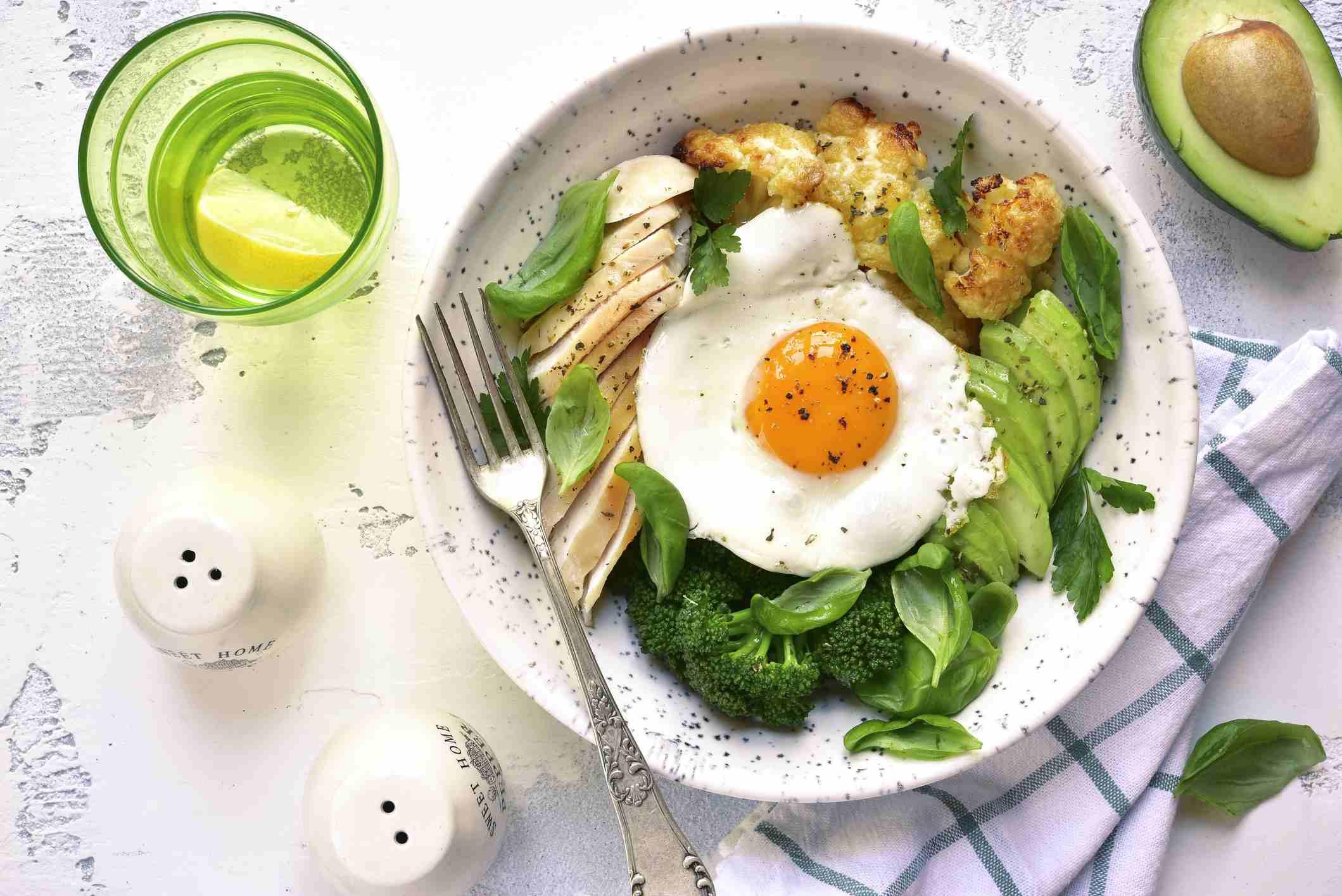 eggs, broccoli, avocado, chicken, and cauliflower in white bowl