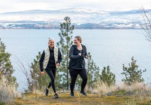 dos mujeres corriendo juntas en las montañas en invierno