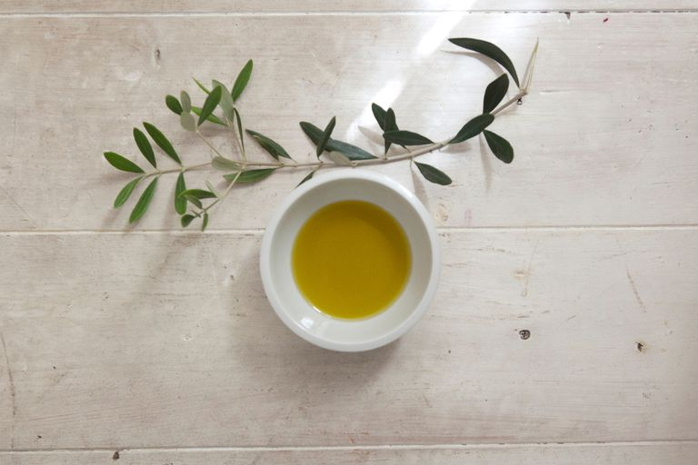 olive oil in bowl on wooden table