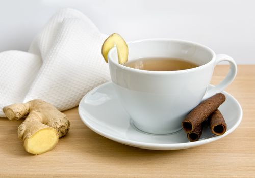 Ginger tea in teacup with fresh ginger on table