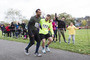 Spectators cheering for man helping injured marathon runner