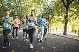 Group of people running track together in a park