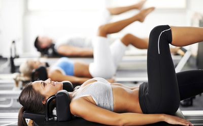 Group of young people exercising on a Pilates machine.