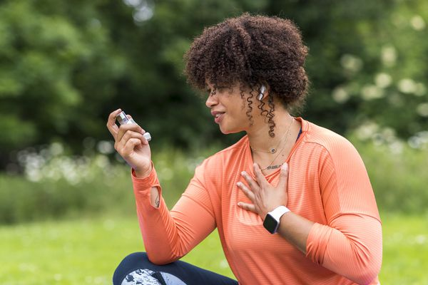 A mixed-race mid adult woman holding her asthma inhaler with her hand on her chest, she is catching her breath.