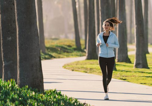 woman running in park on road