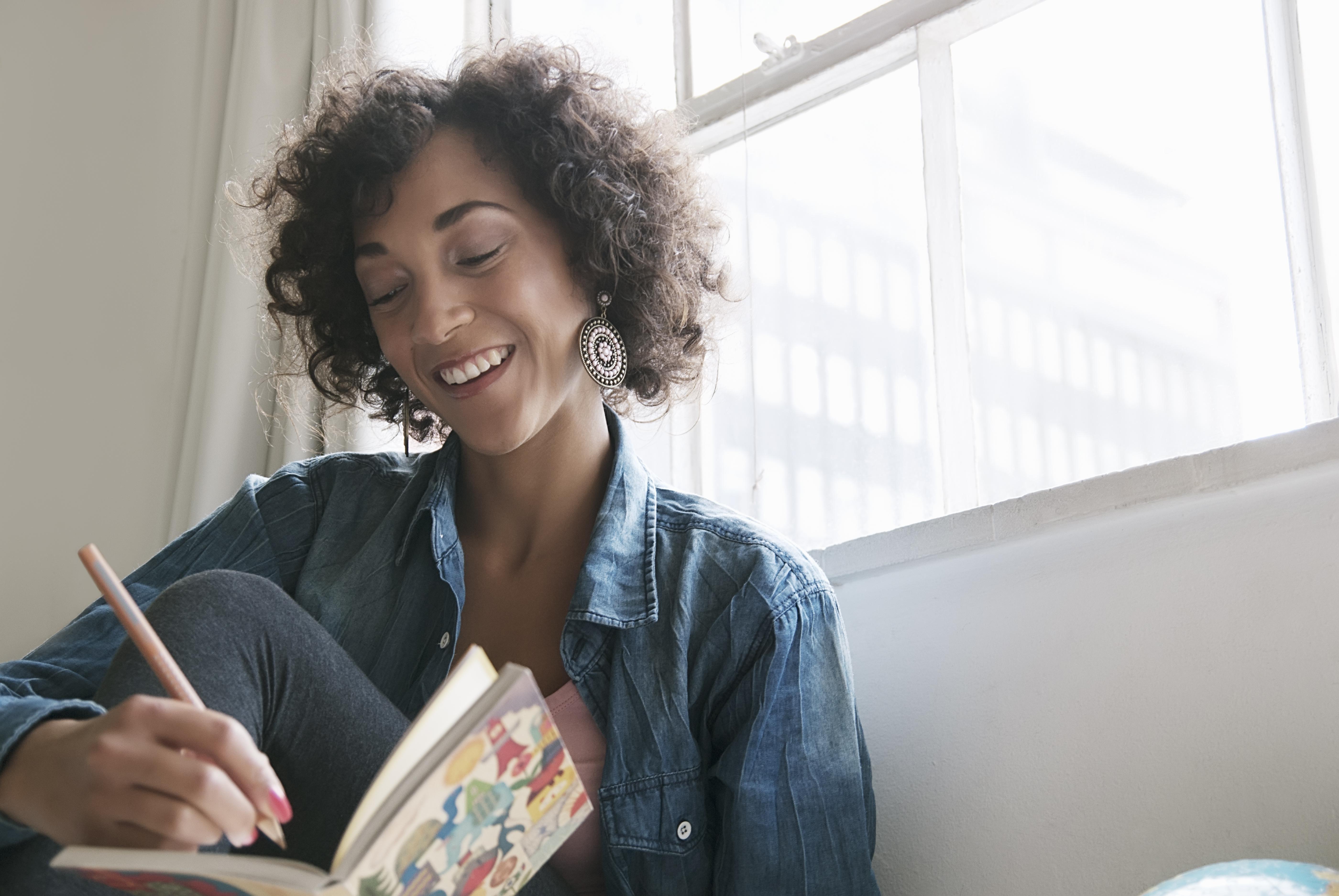 Mujer sonriente escribiendo en diario