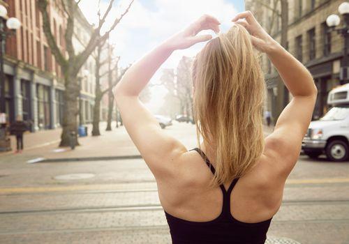 Vista trasera del joven corredor femenino estirando los brazos en la calle