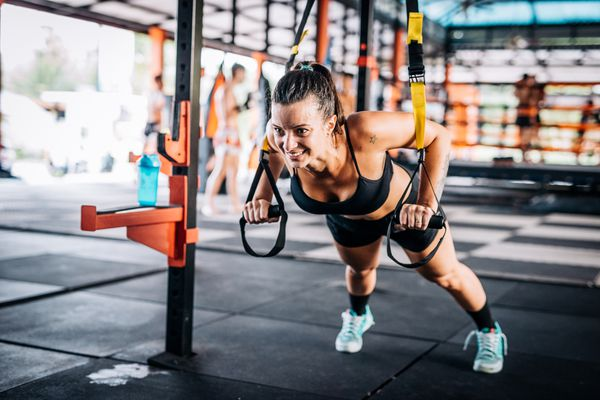 Woman exercising on stretching cords during suspension training