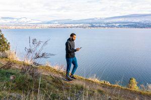 man walking along coastal mountain trail and checking phone