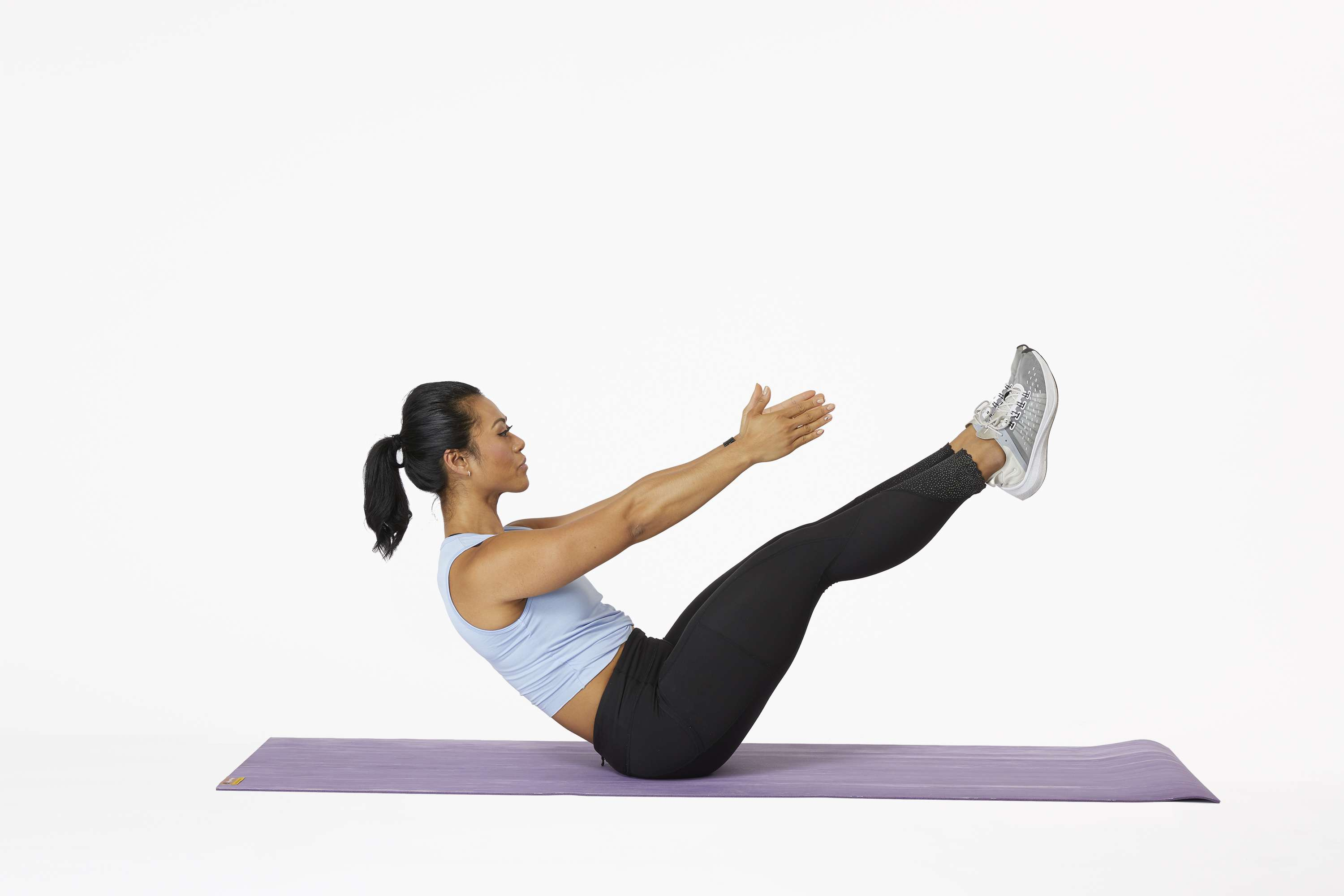 Woman on yoga mat doing a v-sit exercise