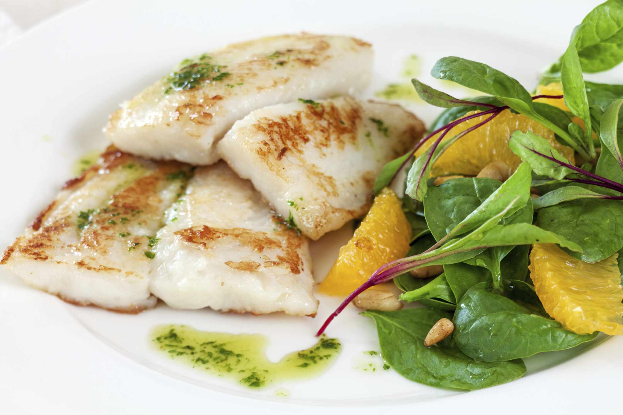 Sauteed fish on a plate with spinach and orange slices
