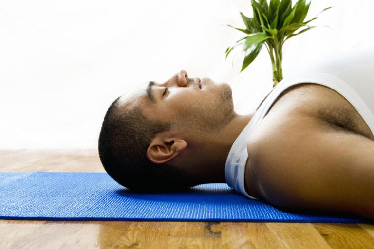 Young man relaxing on exercise mat, side view