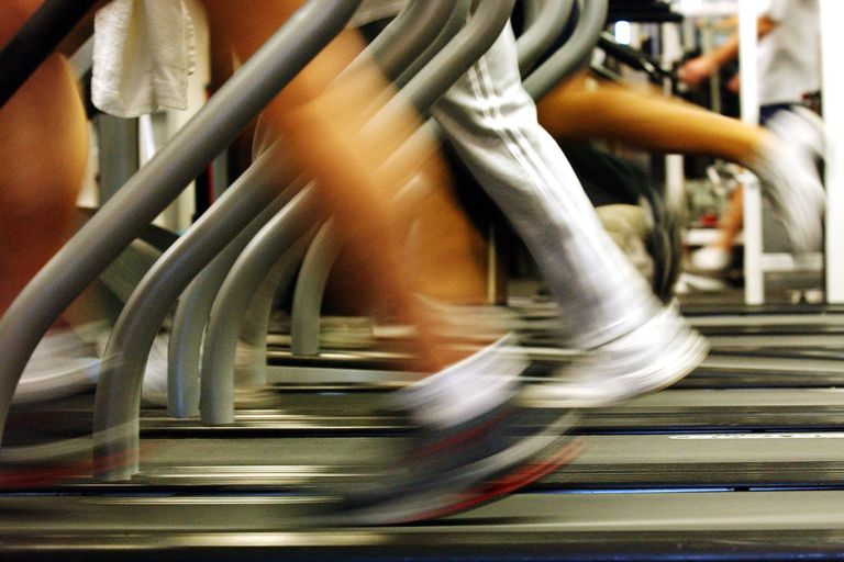 Blurred legs running on treadmills at the gym