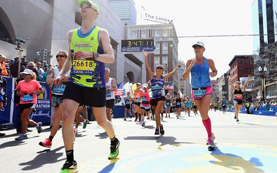 Runners react after crossing the finish line to complete the 120th Boston Marathon on April 18, 2016 in Boston, Massachusetts