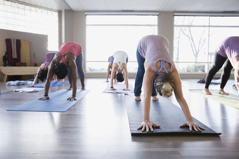 Women practicing downward facing dog in yoga class