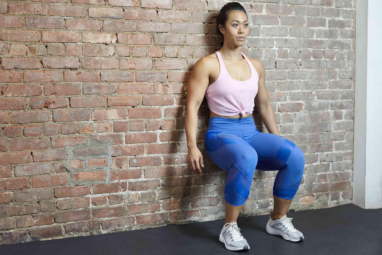 Mujer haciendo una pared sentarse contra una pared de ladrillos en el gimnasio
