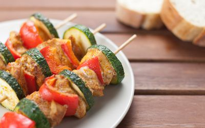 Chicken kabobs with skewer and zucchini on plate