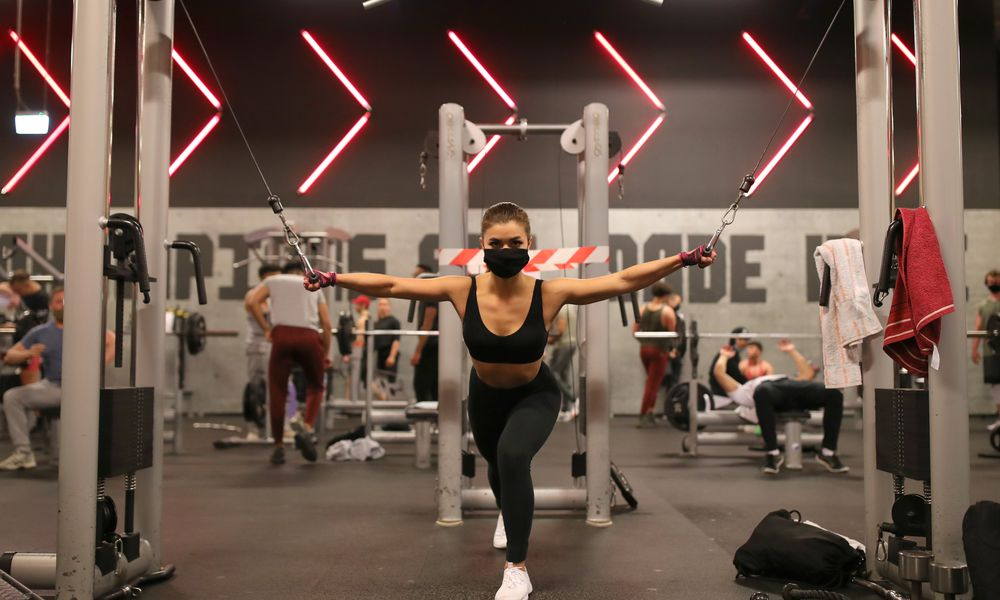 Woman at the gym, wearing a face mask, black sports bra, leggings and white sports shoes. She is pulling on weights with both arms outstretched