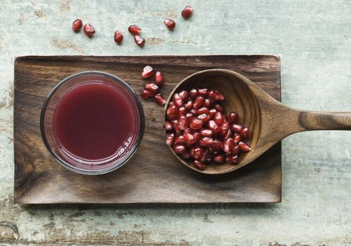 Glass of pomegranate juice and wooden spoon with pomegranate seed on wooden tray
