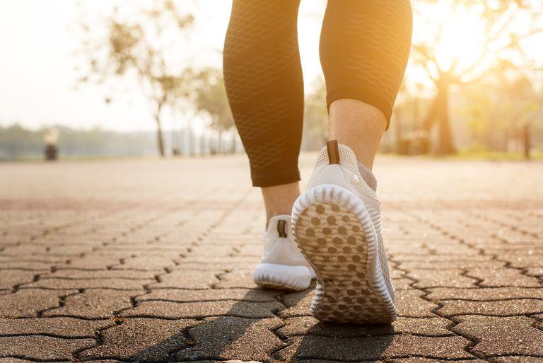 Woman's sneakered feet walking on road