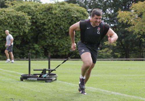 Jugador de rugby corriendo mientras tira del trineo
