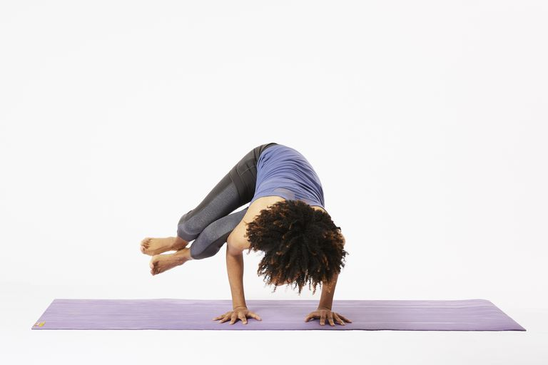 Woman on yoga mat in side crow pose