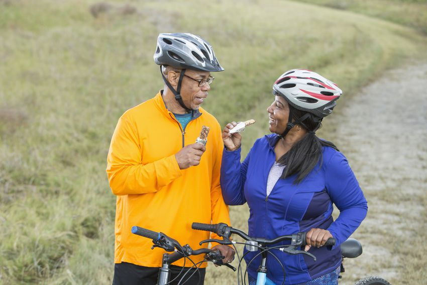 African American couple with bikes, eating snack