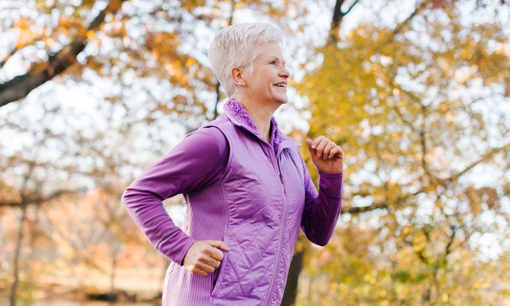 Senior woman running in a purple vest