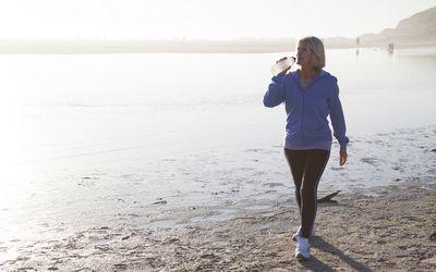 Woman Drinking Water Walking on Beach