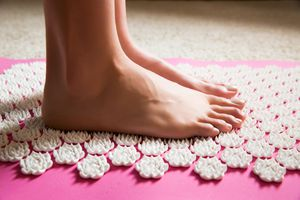 Person standing on acupressure mat