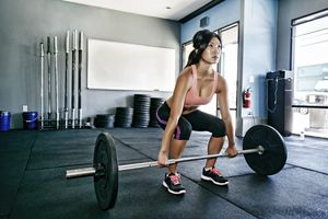 Woman doing deadlifts in a gym