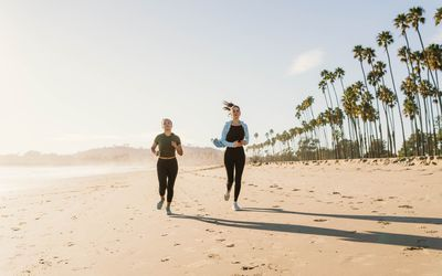 two women running on the beach in the morning