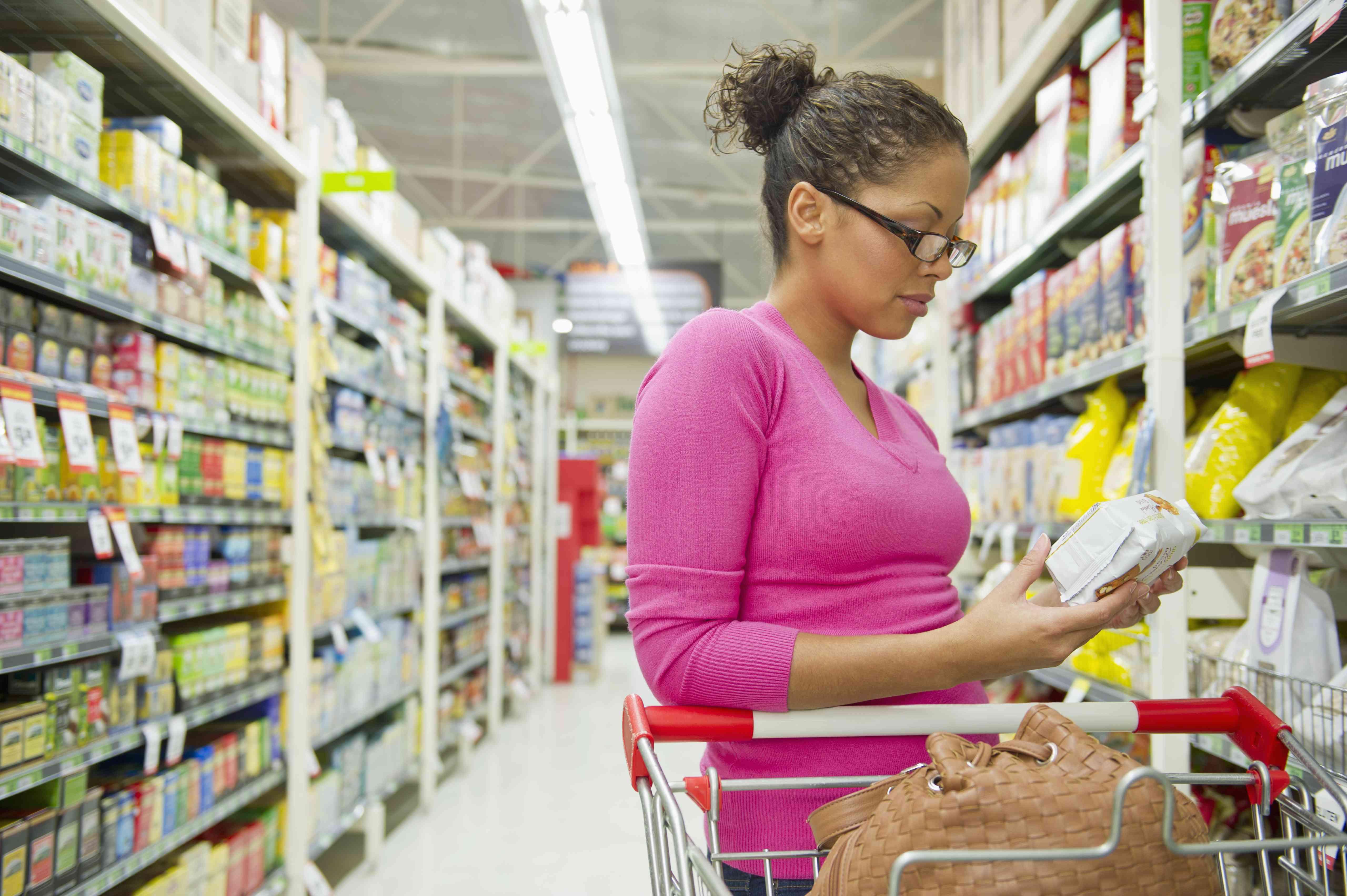Mujer mirando la etiqueta nutricional de un producto en una tienda de comestibles