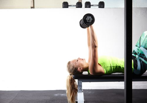 woman doing horizontal dumbbell chest press