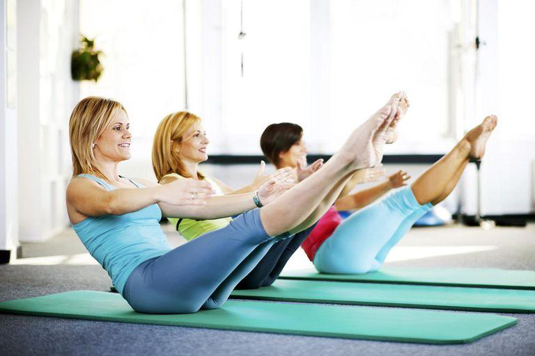 Women doing Pilates exercises on an exercising mat.