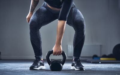 A woman prepares to lift a kettlebell in a CrossFit gym