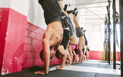 Four CrossFit athletes perform handstand push-ups against a red and white wall.