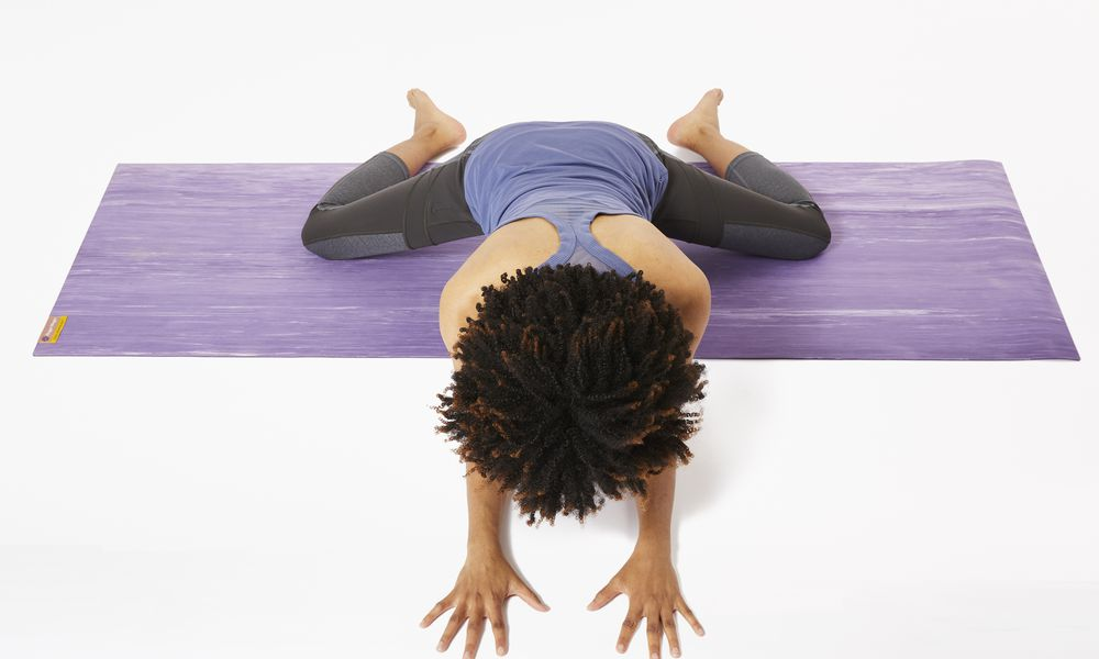 Woman on yoga mat doing frog pose