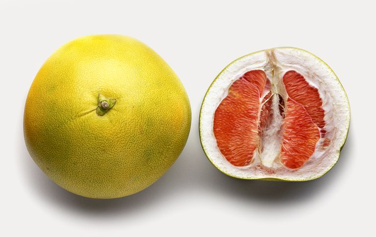 Pomelo fruit, whole and sliced in half