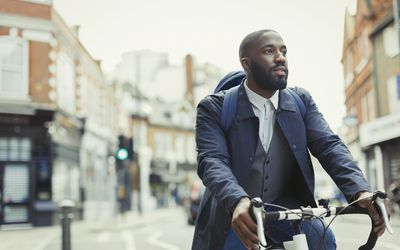 African businessman commuting, riding bicycle on urban street