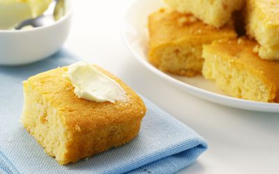 Cornbread with butter on top in front of plate of cornbread slices