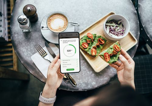 Women using a calorie counting app at breakfast