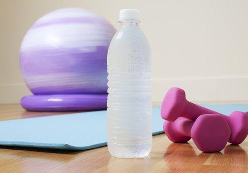 Pelota de ejercicio, pesas rosas, colchoneta y botella de agua