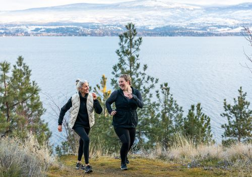 two women walking together on a coastal mountain trail