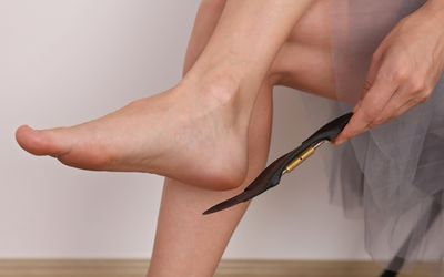 Woman holding orthopedic insole next to her foot