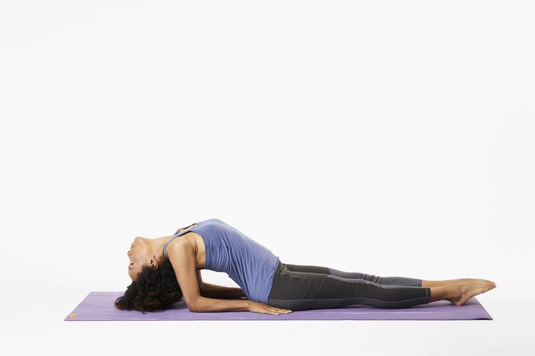 Woman lying on yoga mat in fish pose