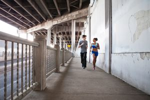 Young couple running on city bridge