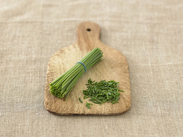 Chopped and whole chive stems on chopping board